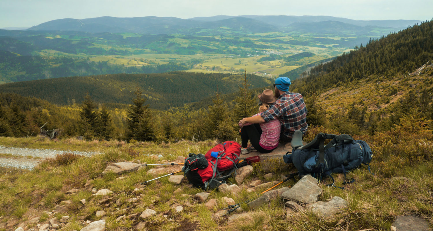 A couple sitting together enjoying a view of hilly Czech Republic countryside while walking from Prague to Budapest