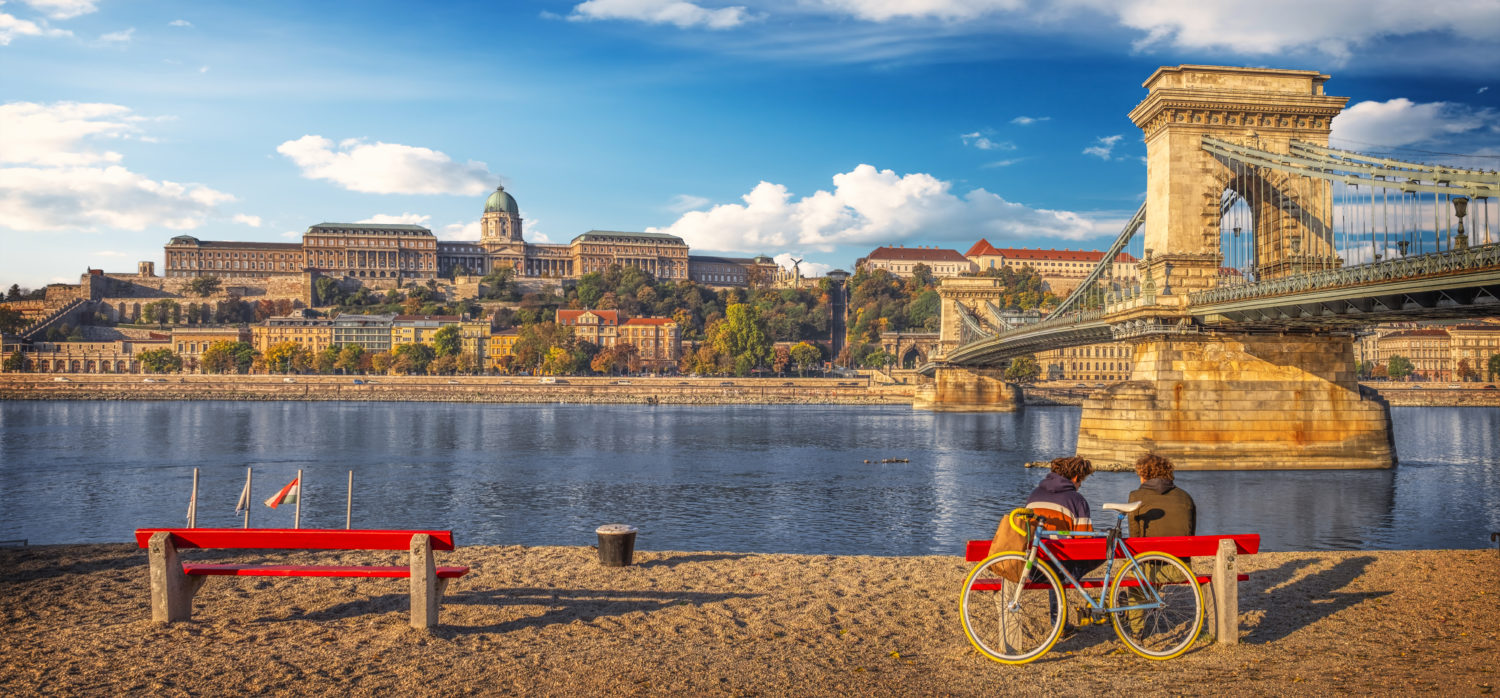 A couple with bikes sitting on a bench overlooking Danube river embankment in Budapest, Hungary