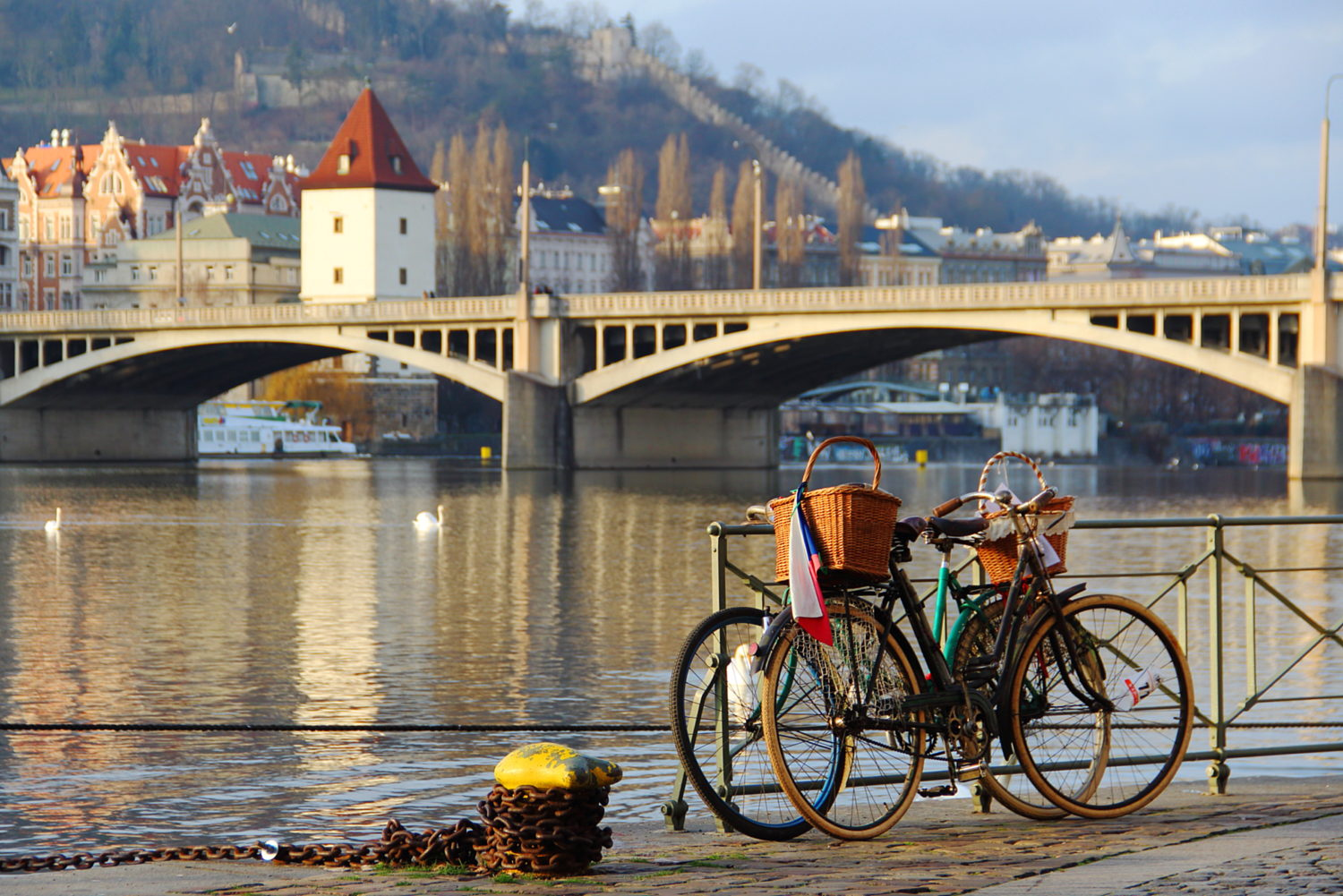 Bikes with baskets by the riverside for cycling from Prague to Budapest