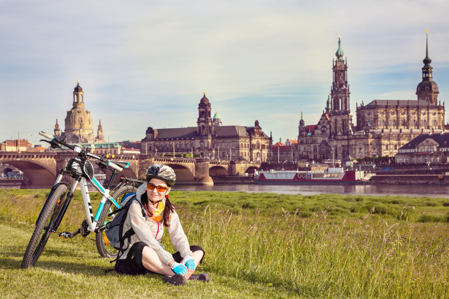 Female cyclist sitting on grass and resting with Old Town of Dresden, Germany in the background
