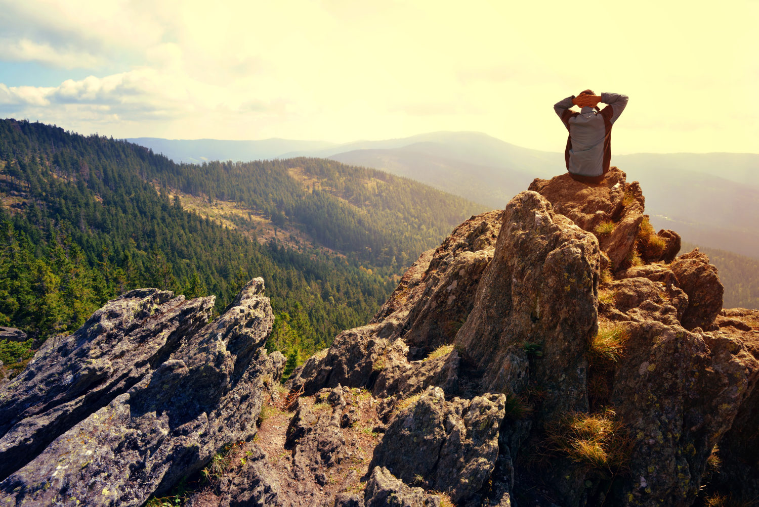 Hiker on the top of a mountain in National park Bayerische Wald, Germany while walking from Prague to Munich