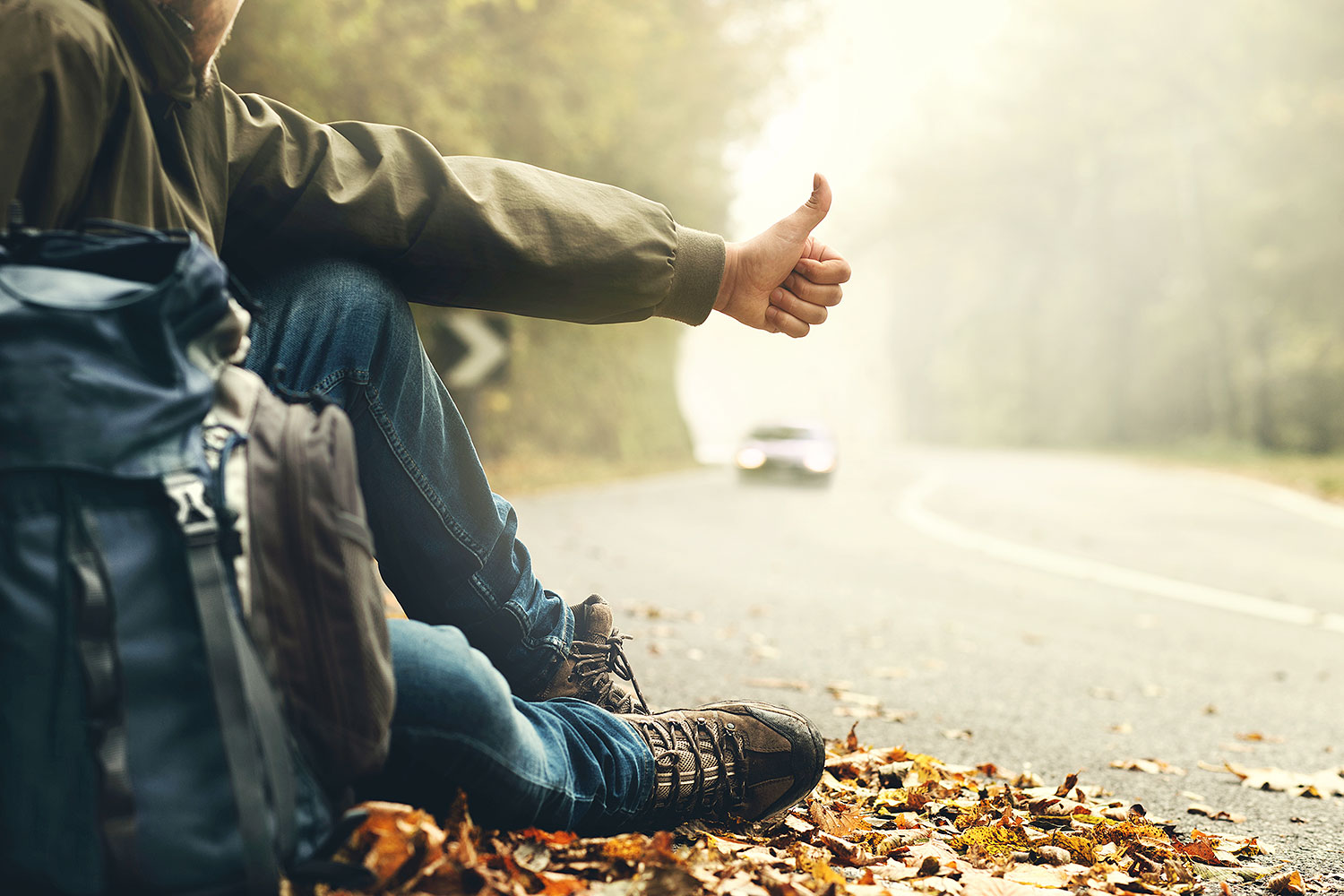 Man sitting on the road with backpack hitchhiking