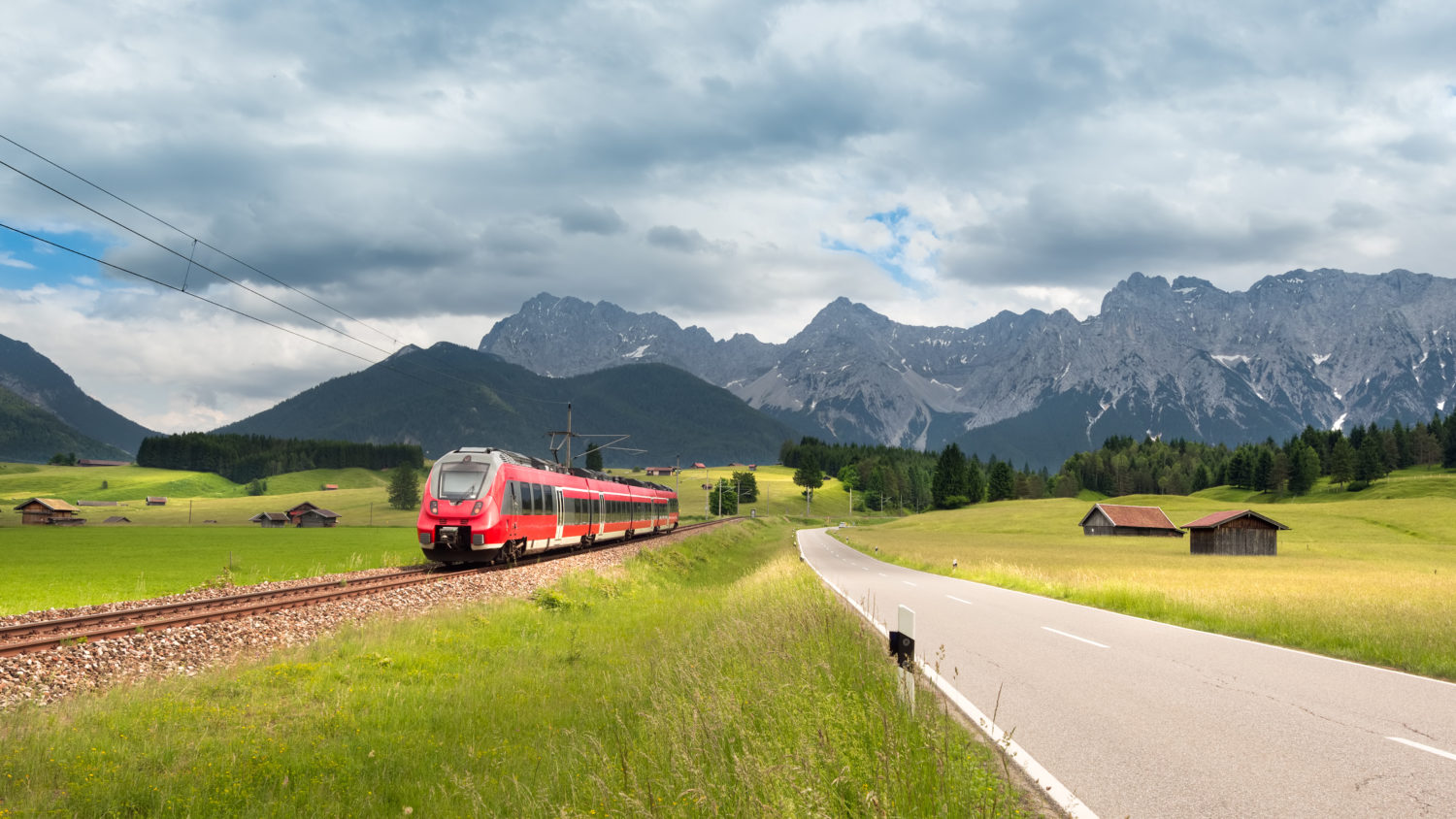 Red train travelling from Prague to Munich with mountains in the background
