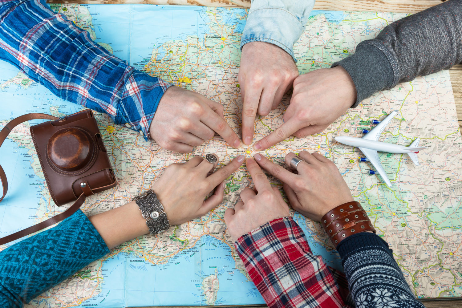 Six hands pointing at Munich with an airplane miniature and vintage camera case placed on the map of Europe