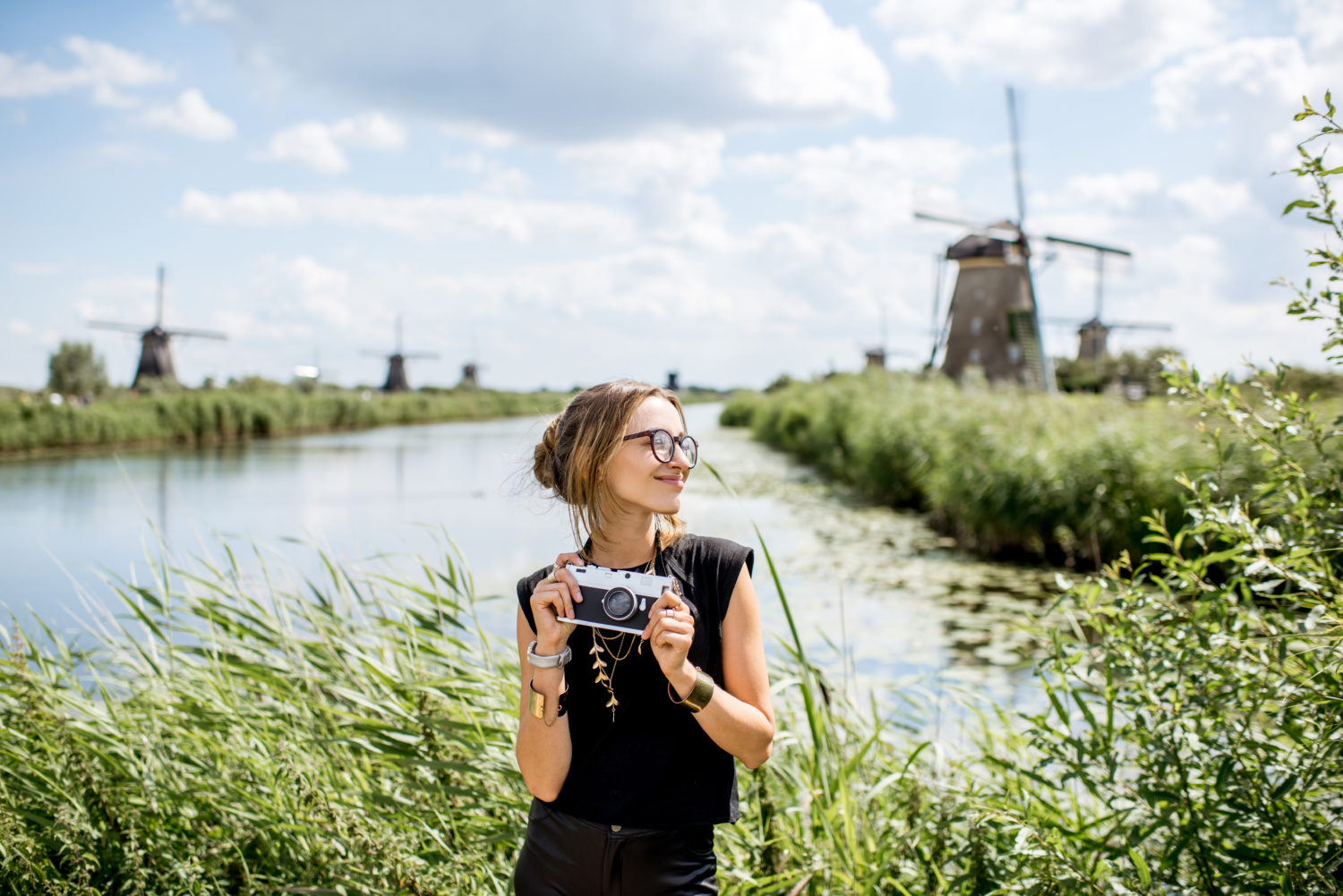 Smiling woman with a camera standing next to a canal in Netherlands with windmills in the background