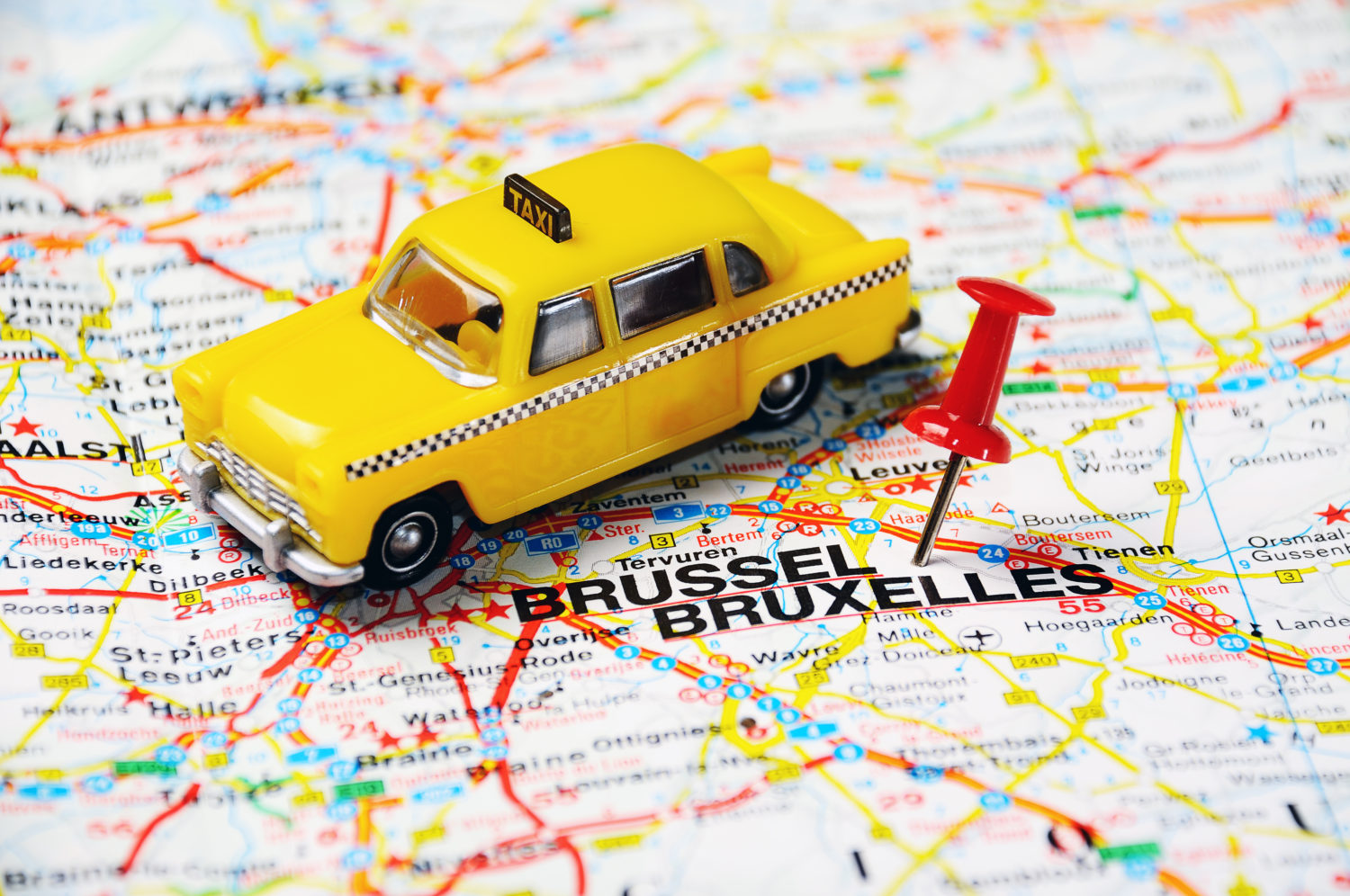 Taxi car miniature on a map of Belgium with a red pin next to Brussels