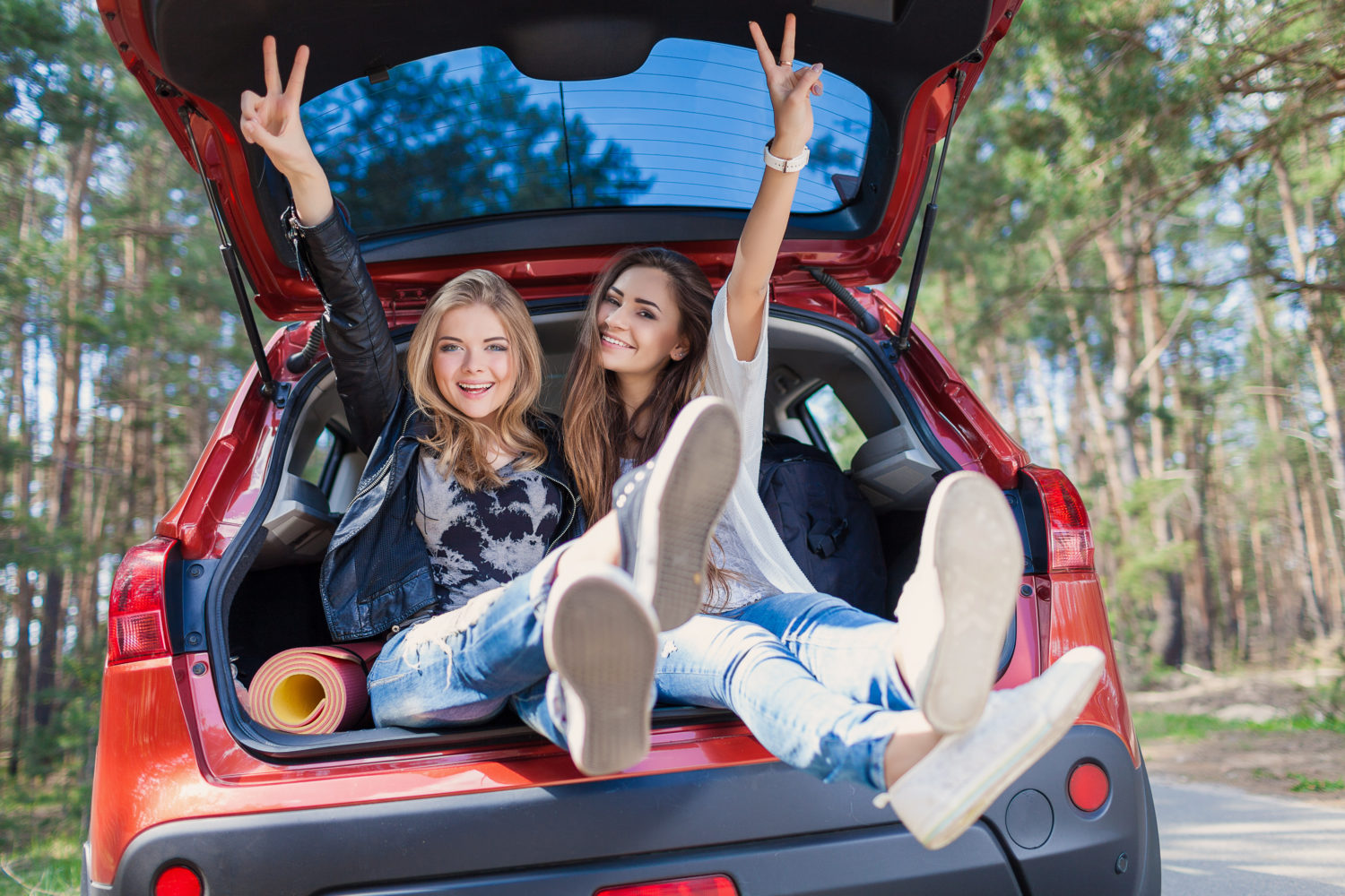 Two happy young women sitting in a parked car boot while car sharing from Prague to Budapest