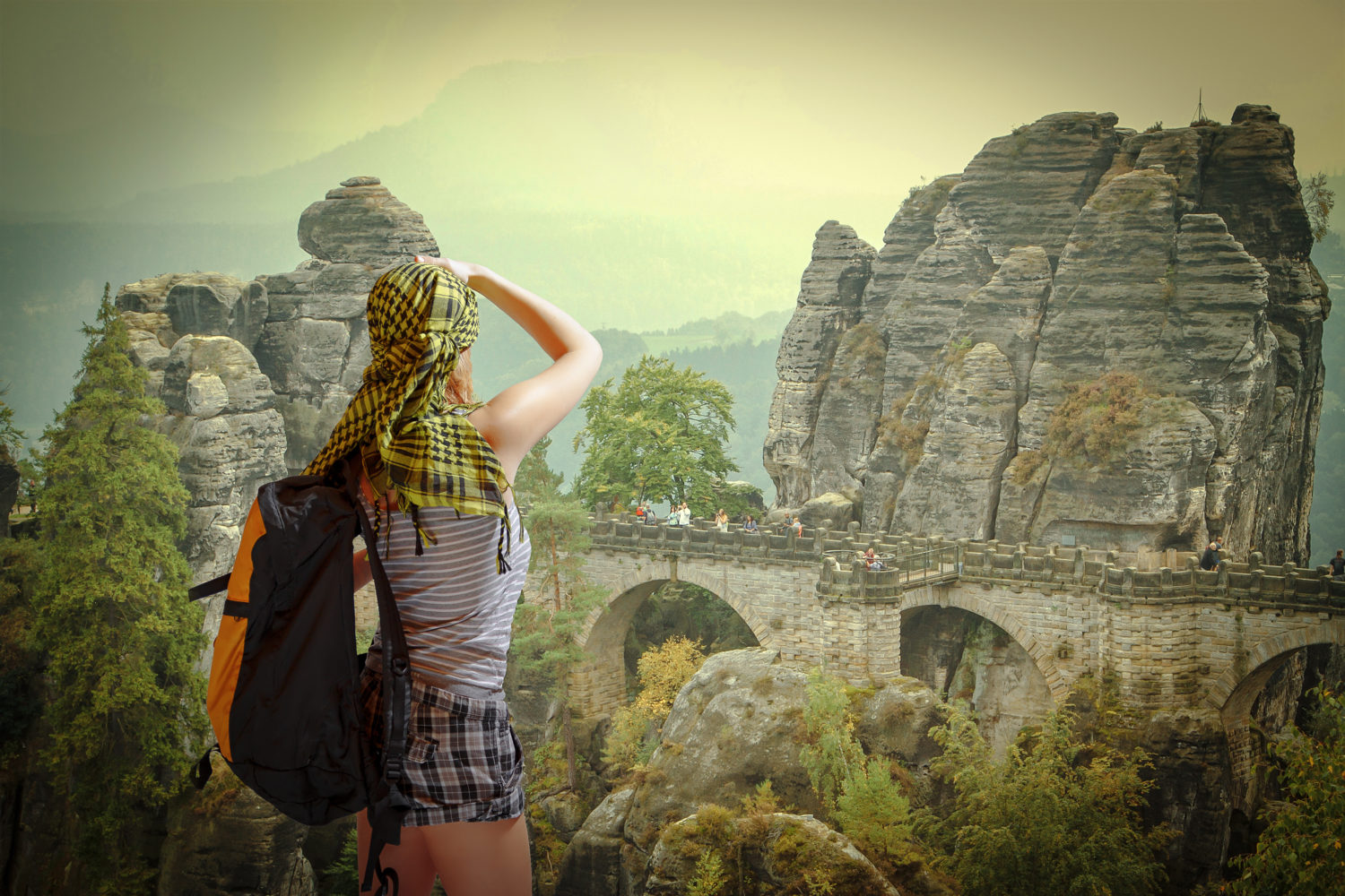 Woman with backpack walking from Prague to Berlin in Saxon Switzerland Germany