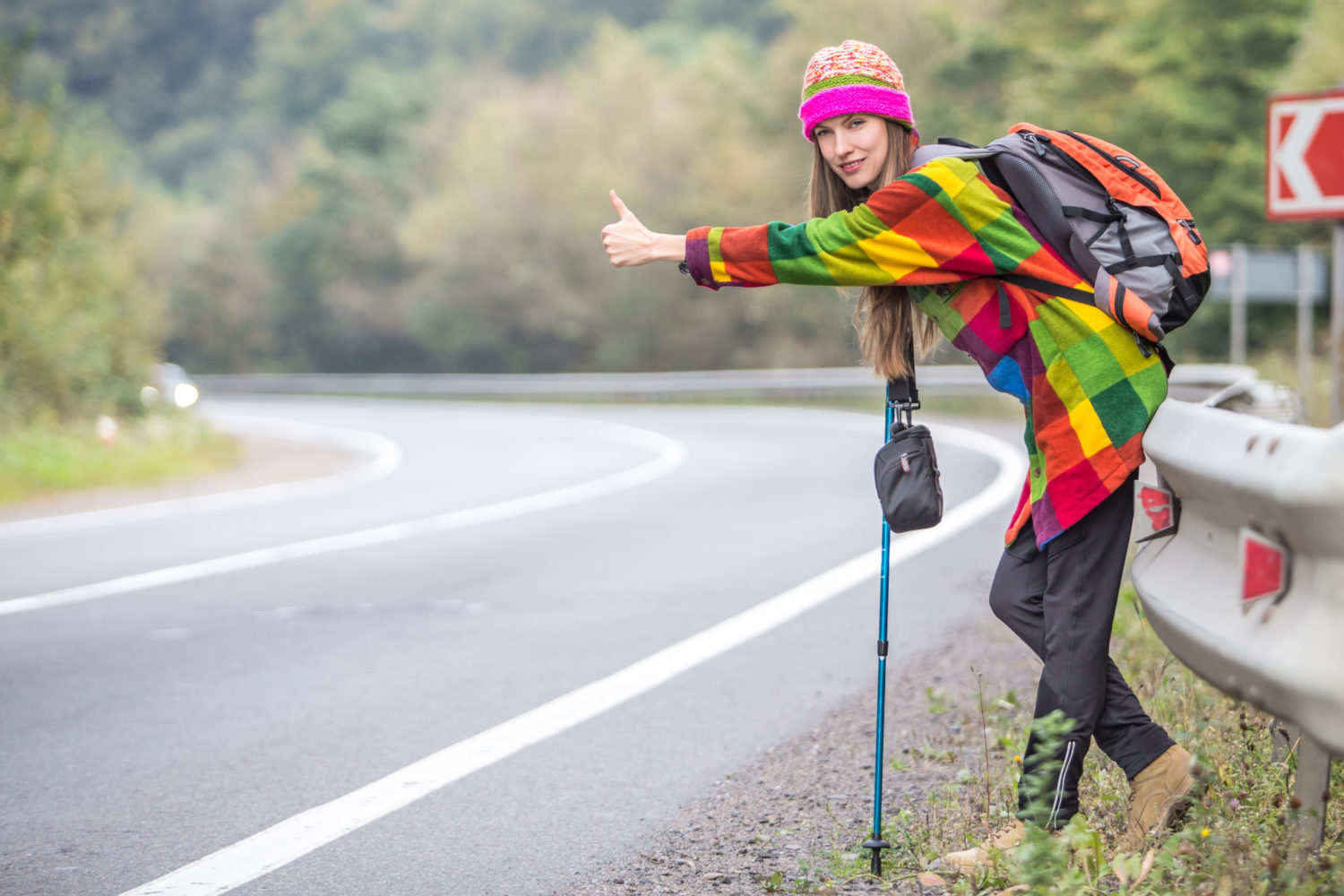 Young woman hitchhiking on a road from Lisbon to Faro