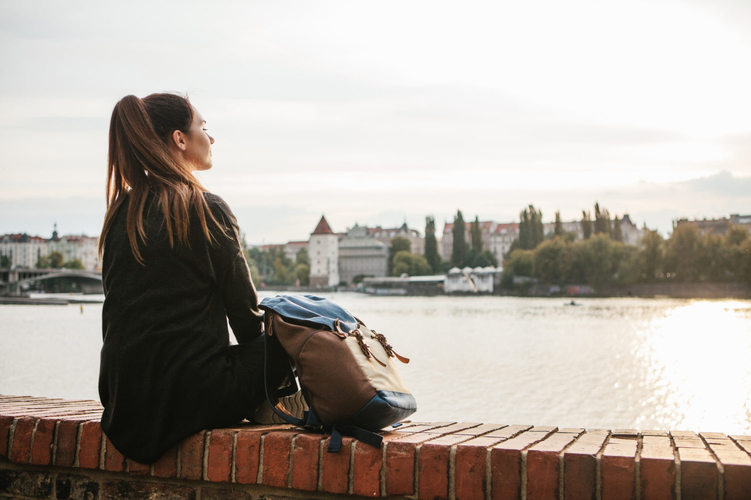 Young woman sitting on a wall in Prague with a bag next to her overlooking the river