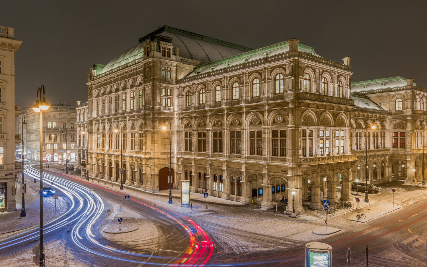 Vienna state opera in the winter night with traffic surrounding it