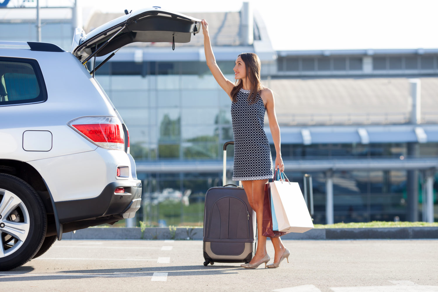 Young professional woman with bags next to a private transfer car from Prague to Vienna