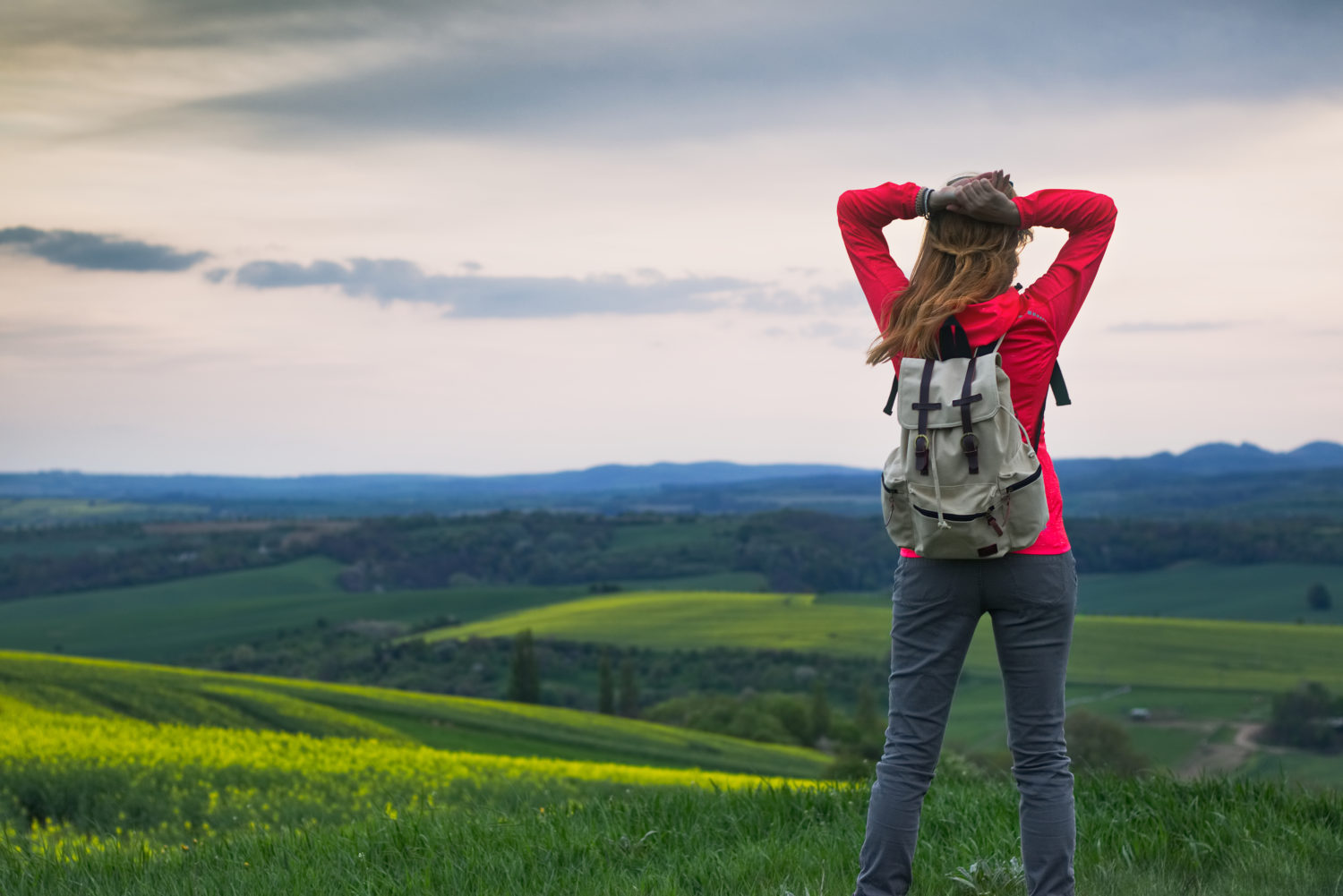 Young woman in red blazer with gray backpack looking at a view of Czech countryside while walking from Prague to Vienna