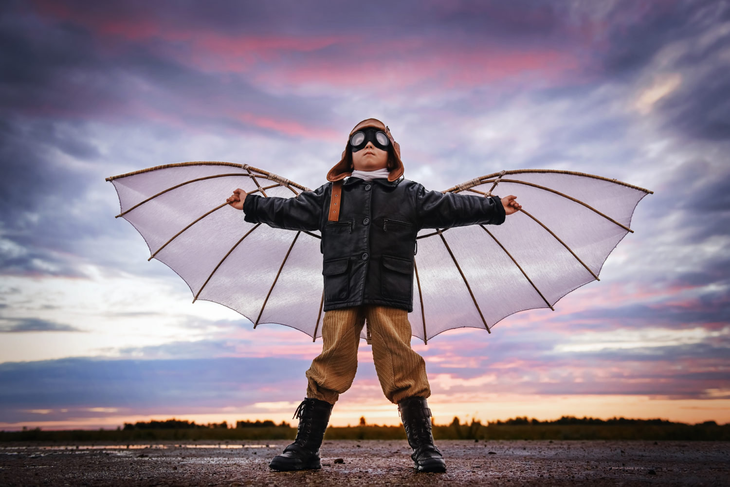 Little boy in retro pilot outfit with wings
