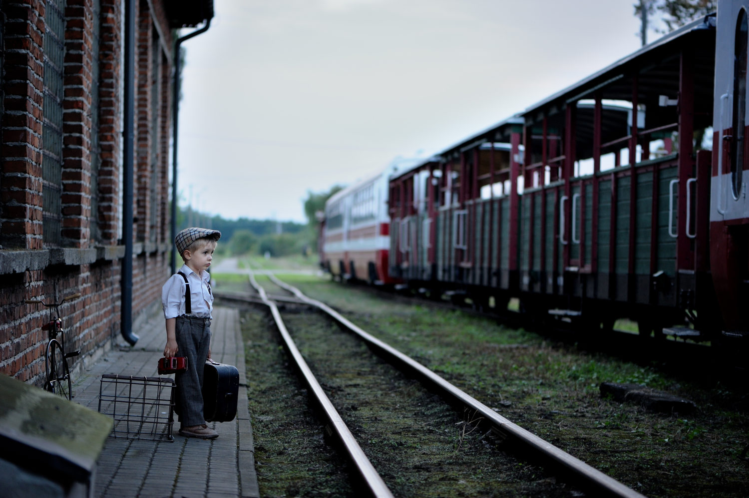 Little boy standing on an empty train platform waiting for a train from Riga to Vilnius