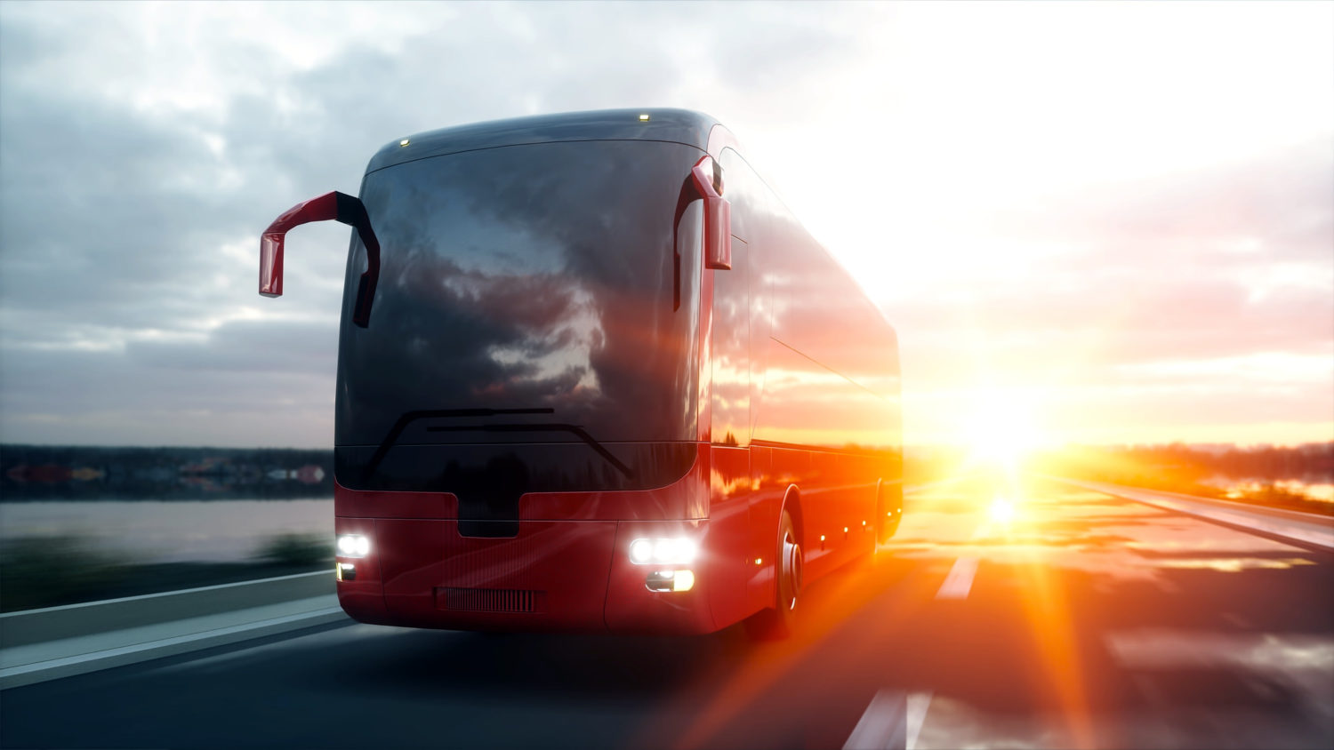 Red bus driving on a road with sunset behind it from Tallinn to Riga