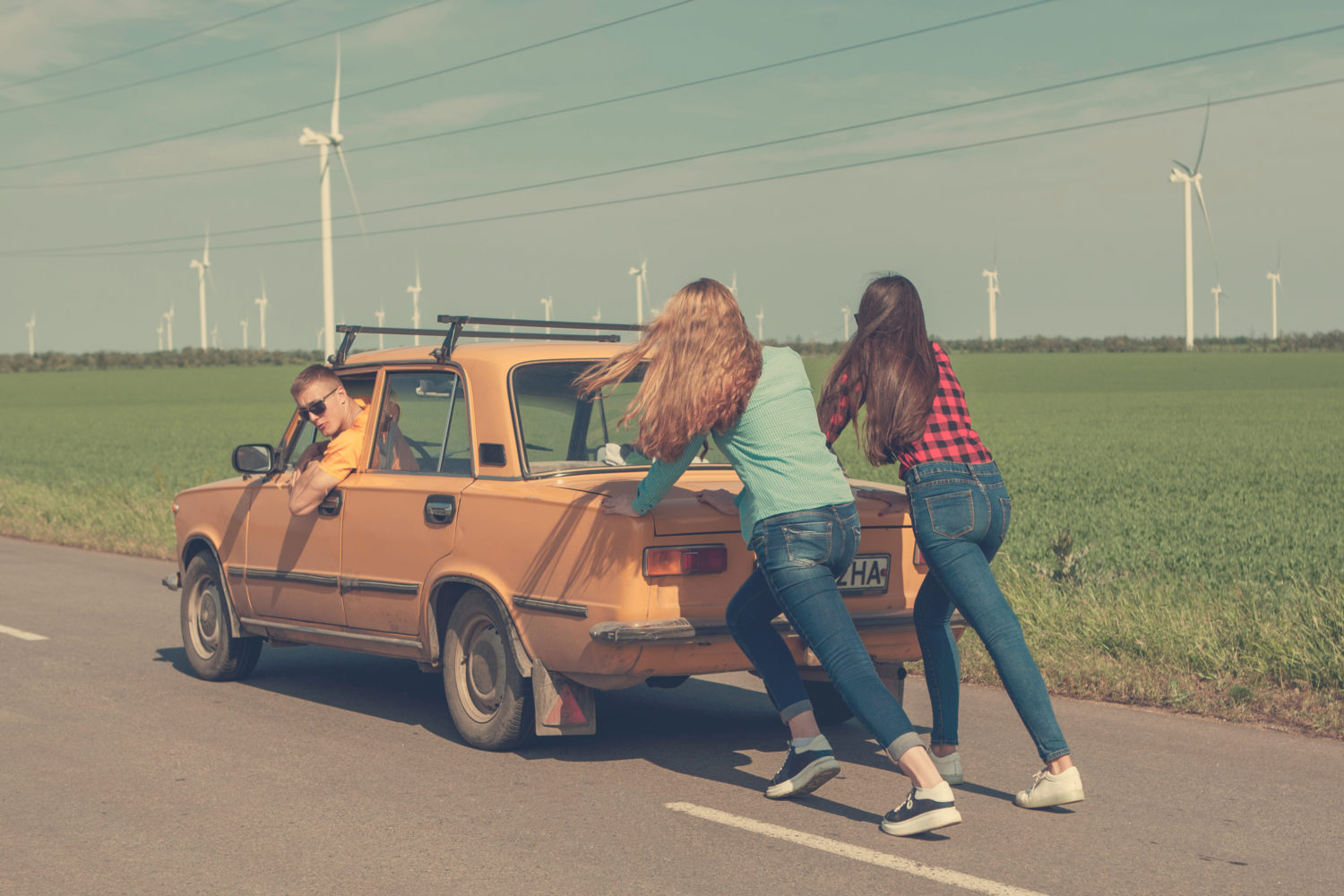 Two girl pushing an old orange Soviet car with a boy in it down the road while on a road trip from Riga to Vilnius