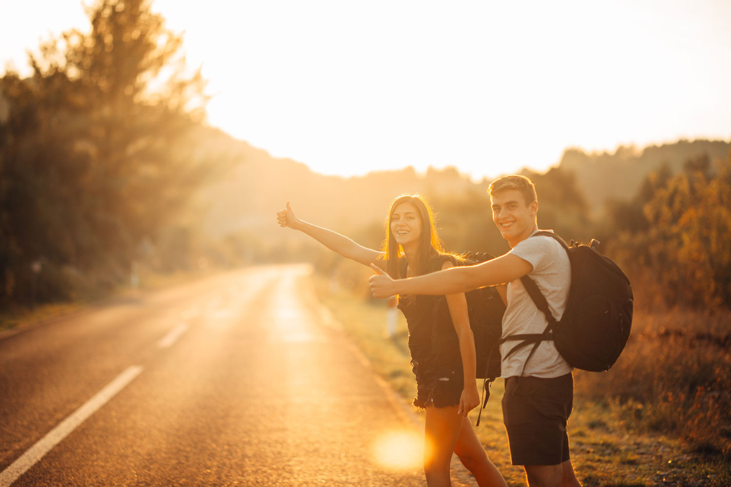 Young man and woman hitch-hiking on a countryside road