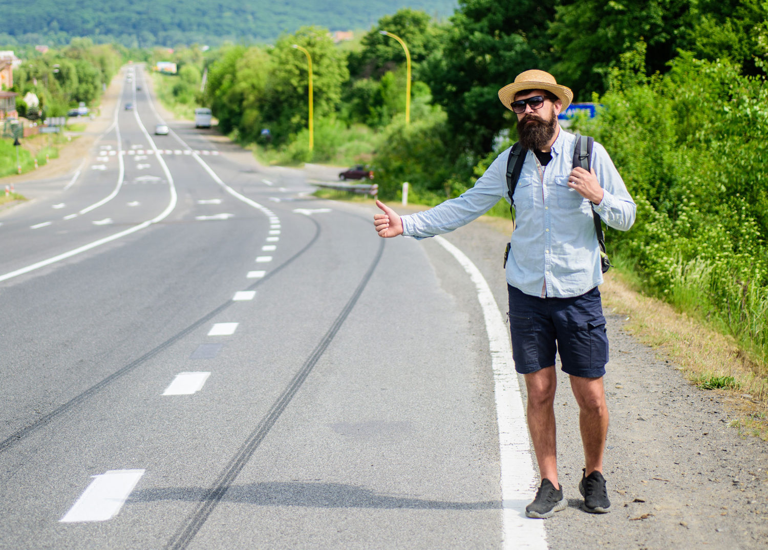 Bearded hipster man hitch-hiking on a road