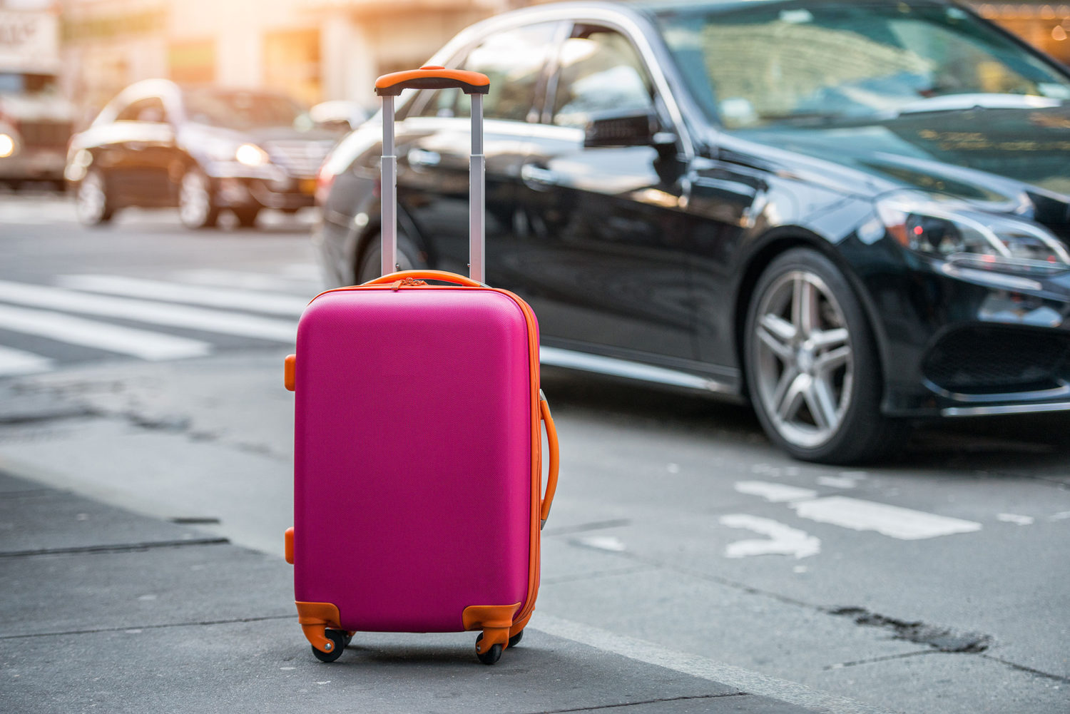 Pink suitcase waiting on a sidewalk with black luxury car in background
