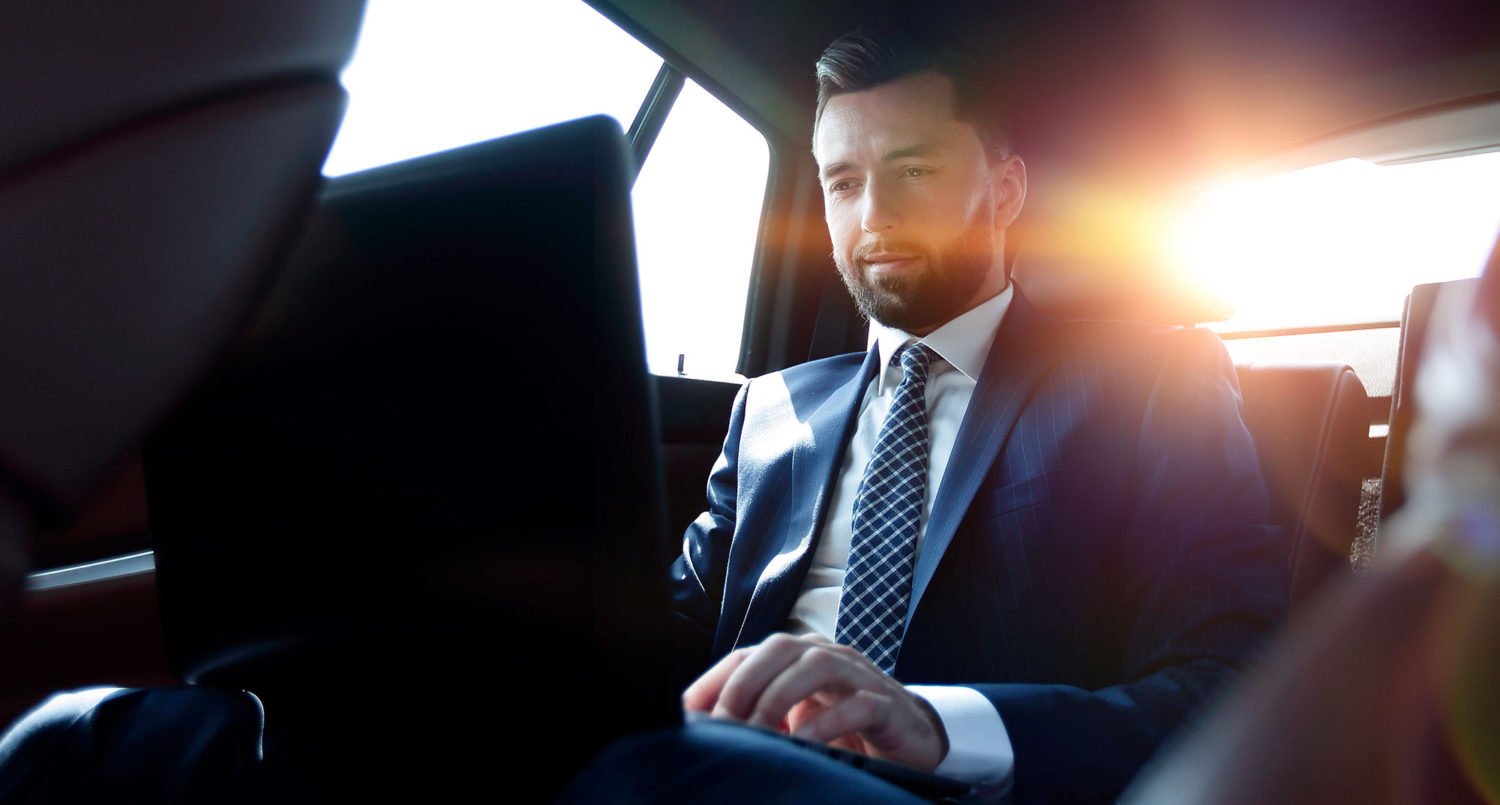 A man in a suit working with a laptop on the backseat of a car
