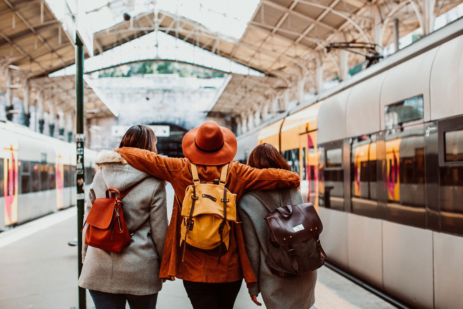 Three women with backpacks walking on a train platform with trains on both sides