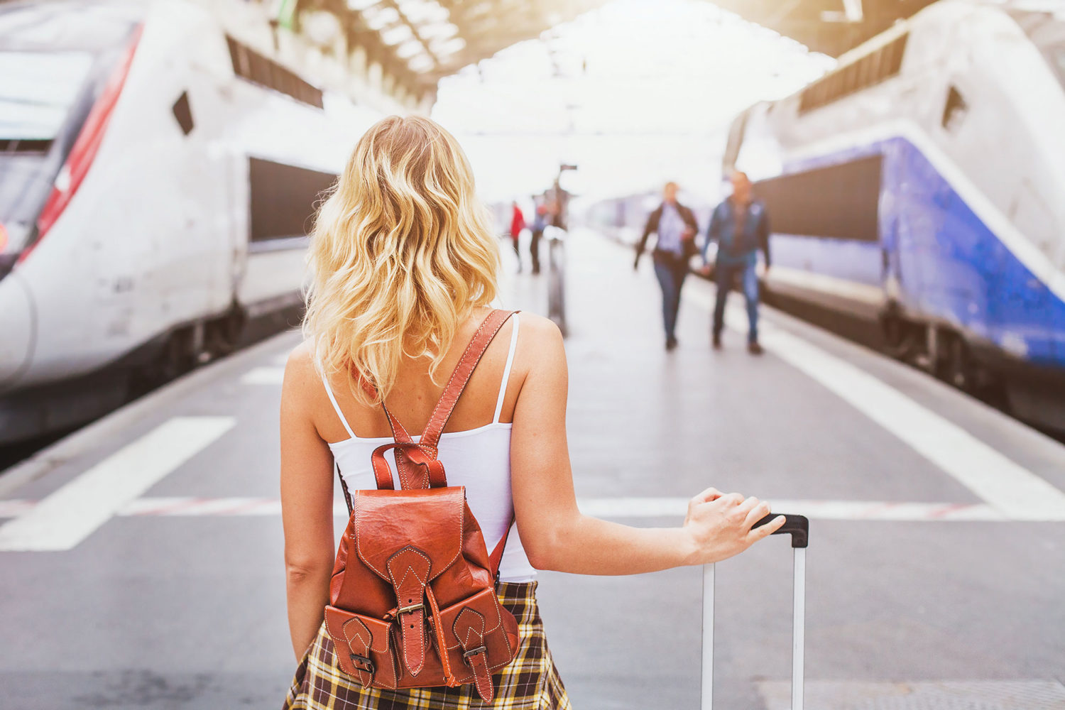 Blond woman with bags walking towards a train platform