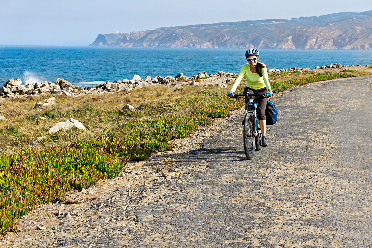 Woman cycling on a seaside road in Portugal