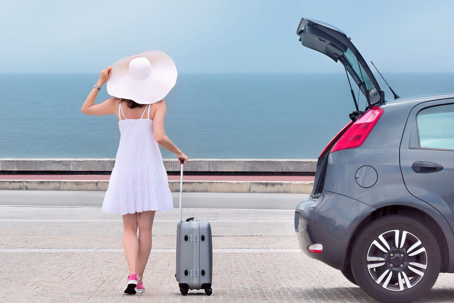 Woman in a big white hat walking towards a private hire car with her luggage