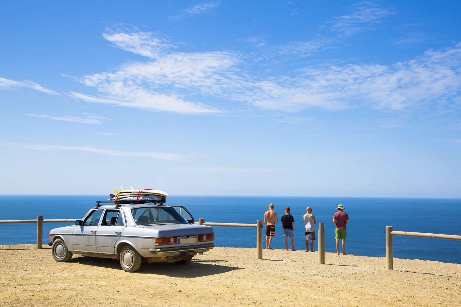 Four men looking at the sea while on a roadtrip in Portugal